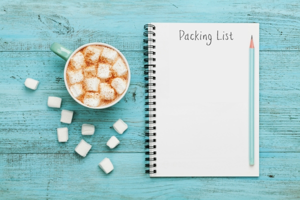 cup of hot chocolate with notepad with packing list
