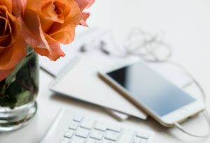 Desk with keyboard, phone and flowers