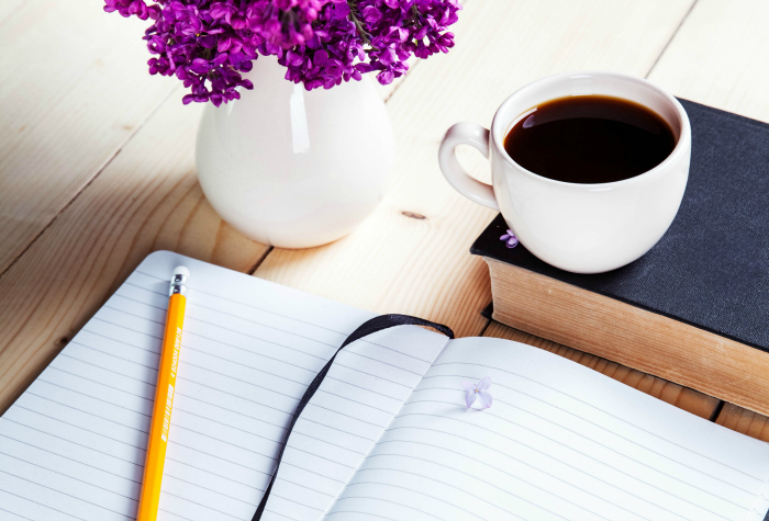 flowers, coffee, and notebook sitting on a table