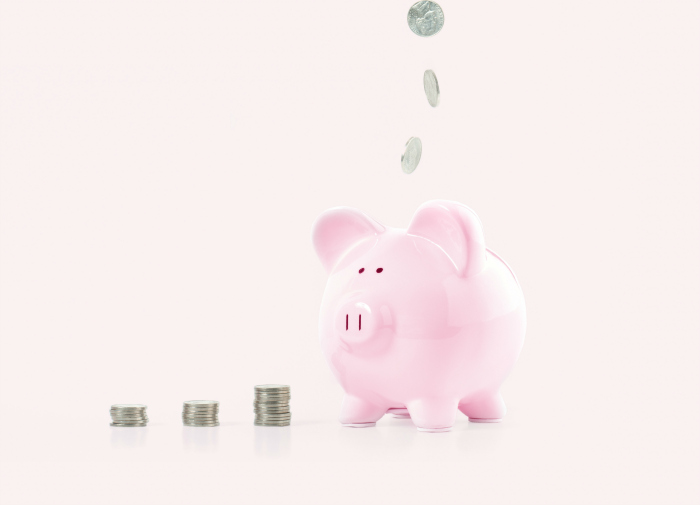 Pink piggy bank on pink background with change being added.