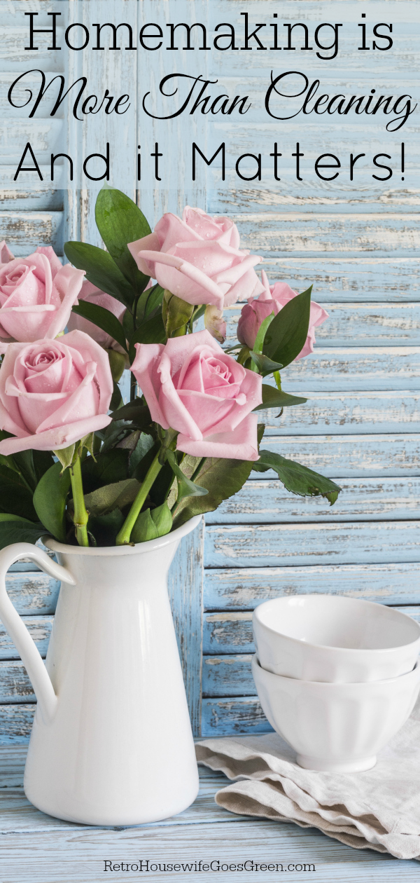 Pink roses in a white enameled pitcher and ceramic white bowls on blue wooden rustic background.