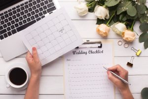 desk with laptop, cup of coffee, roses, and wedding checklist