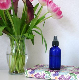 blue spray bottle on floral journal next to fresh flowers