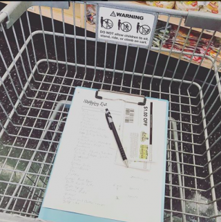 clipboard with shopping list and coupons in cart