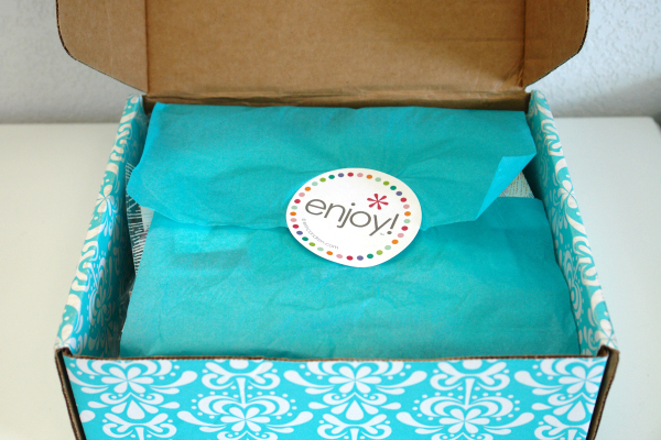 "inside of Erin Condren box with aqua tissue paper and ""enjoy"" sticker"