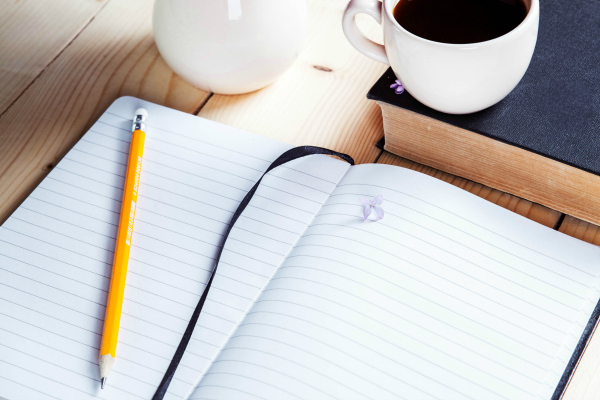 notebook, pencil, and cup of coffee on table.