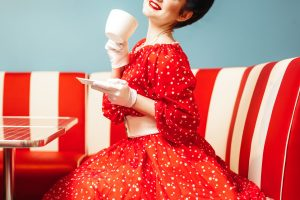 retro housewife in red dress sitting in diner drinking coffee