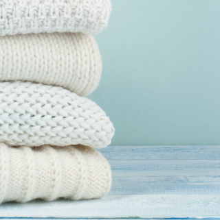 Pile of knitted winter clothes on wooden background