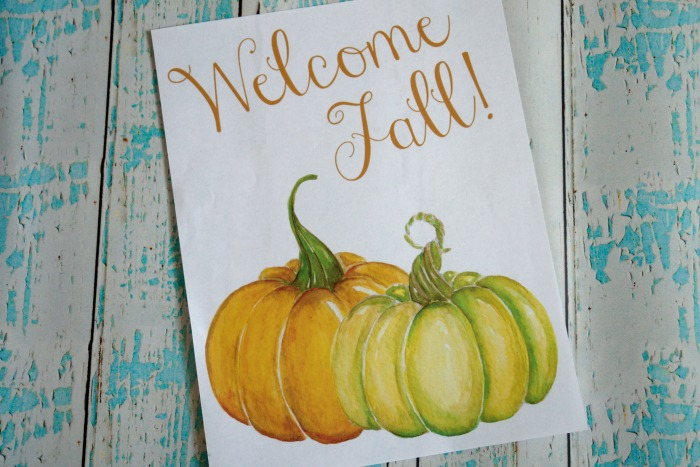 welcome fall sign on aqua and white wooden background