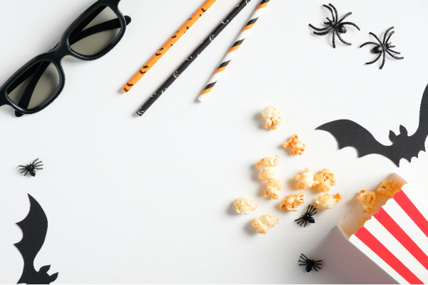 Halloween glasses, popcorn, drink straws, bats, spider on white background.