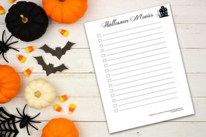 white wooden background with pumpkins and other halloween decorations and halloween movies printable