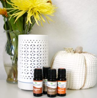 fall flowers, white diffuser, white pumpkin, and essential oil bottles on white table