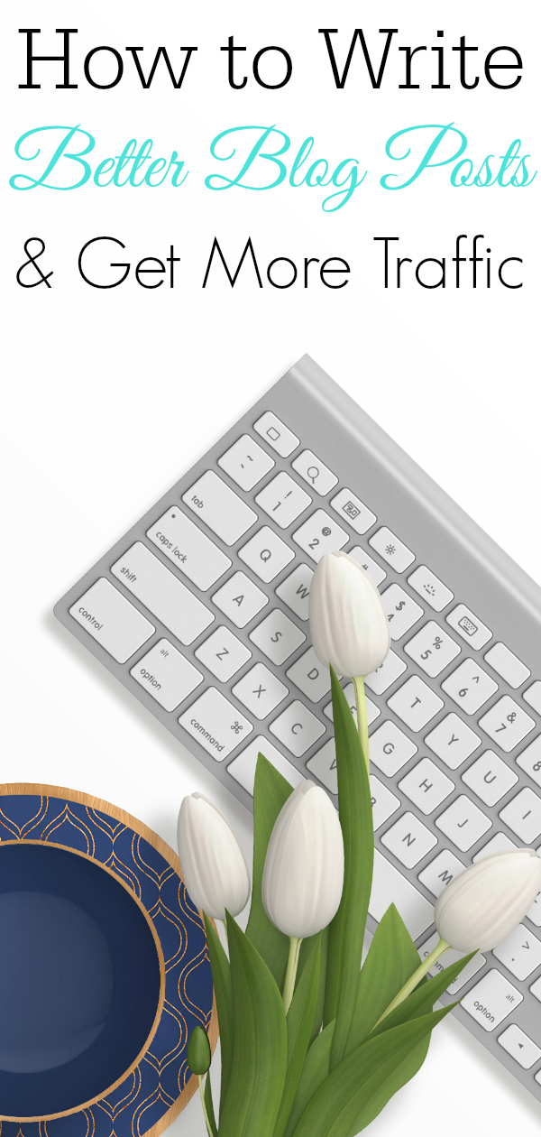 computer keyboard on white desk with blue coffee cup and white flowers