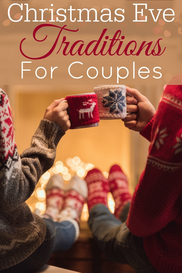 couple in festive socks by fireplace with cocoa