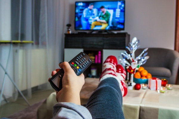 person with remote watching christmas movies