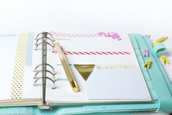 Feminine stationery: colorful paper binder clips palm and flamingo shape on white table background with washi tape.