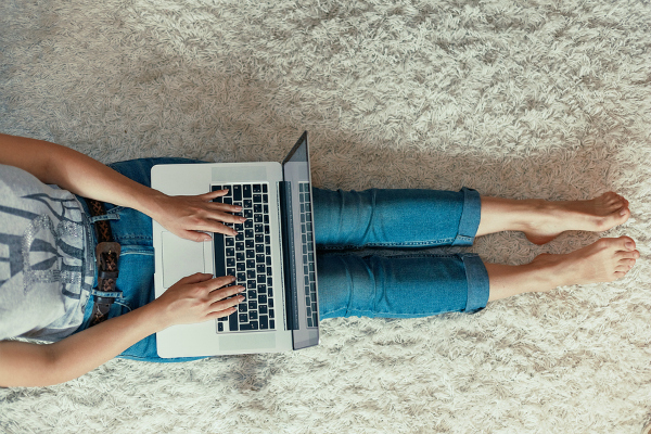 Woman using a laptop sitting on floor