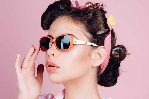 1950's housewife in sunglasses with pink background