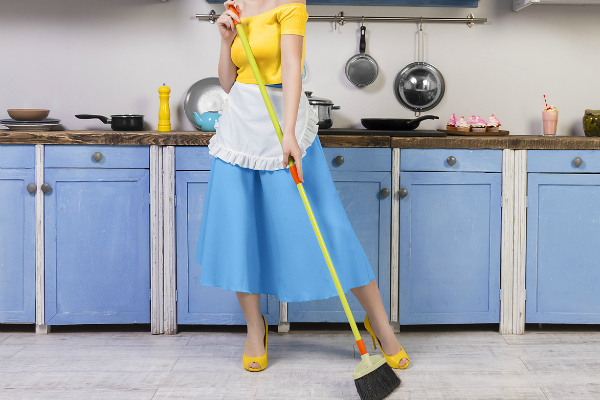 woman wearing a '50s style dress, heels, and holding a broom