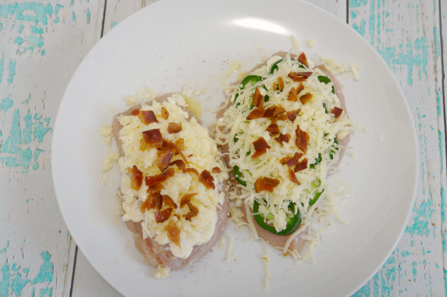 prepped cheesy jalapeno chicken on plate, one without the jalapeños