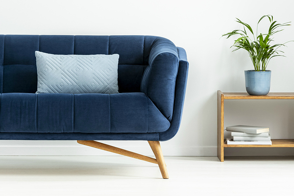 Mid-century modern chair with a blanket and a large sofa with colorful cushions in a spacious living room interior with green plants and white walls.