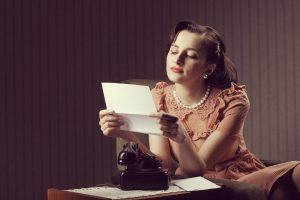 1940's housewife sitting reading a letter next to a black phone