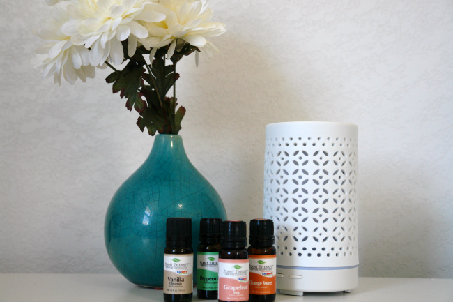 turquoise vase with white flowers, essential oils, and diffuser