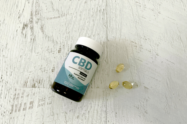 CBD bottle and soft gels on white wooden background