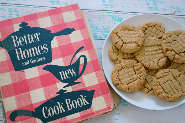 vintage Better Homes & Garden cookbook with peanut butter cookies on a plate
