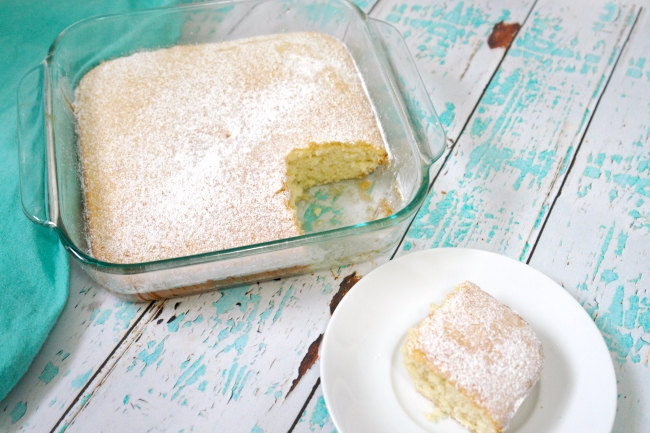 hot milk cake in glass baking dish with one piece on a white plate