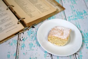 a piece of hot milk cake on white plate next to open vintage cookbook