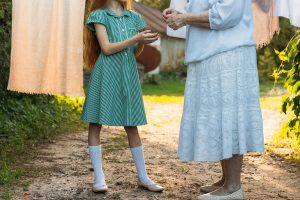 little girl with grandma outside by clothesline