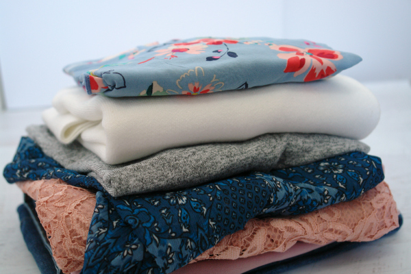 stack of clothing on white wooden background
