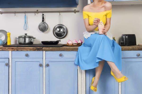 1950s housewife sitting on countertop drinking milkshake, cupcakes in background