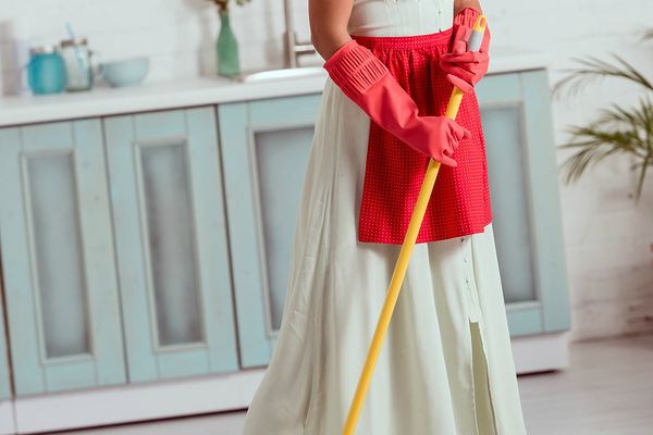 woman in yellow dress with red apron mopping