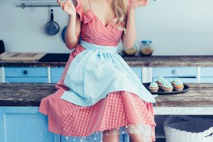 retro housewife with cupcakes in kitchen