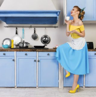 1950s housewife in blue and yellow dress with yellow heels, sipping tea in vintage kitchen