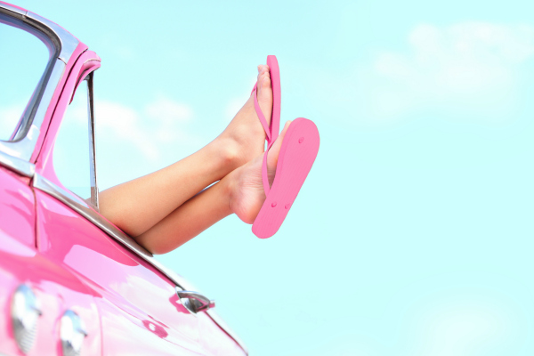 pink vintage car with lady hanging her legs out