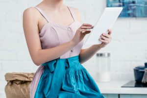 retro housewife sitting on countertop looking at tablet