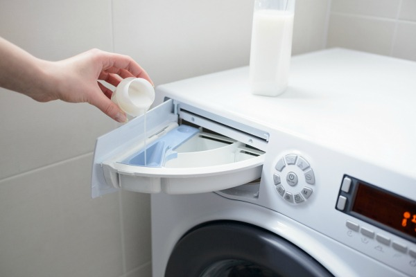 person pouring liquid into washer