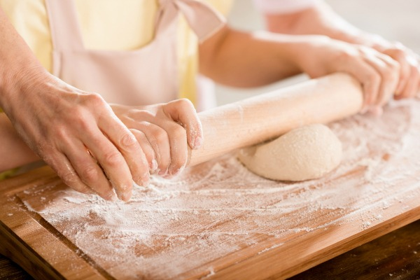 grandma showing child how to roll out dough
