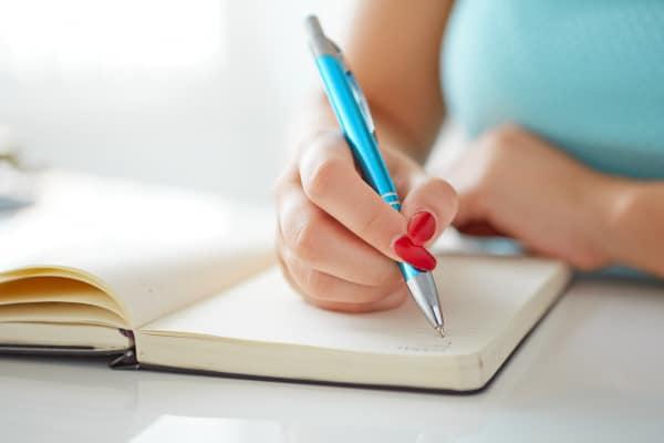 woman writes to-do list on a white table