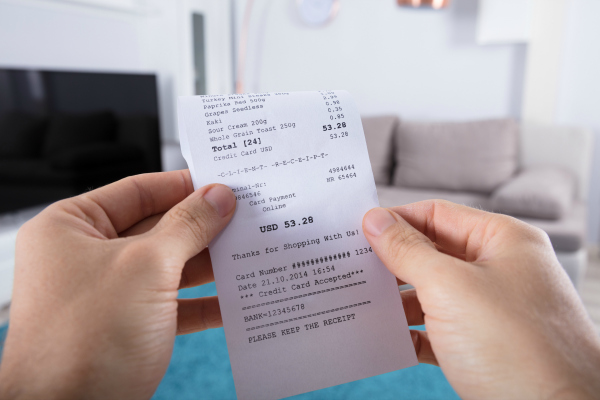 person holding grocery receipt