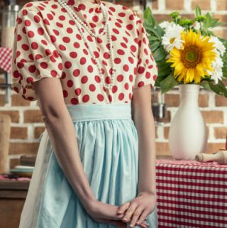 perfect 1950s housewife standing in kitchen