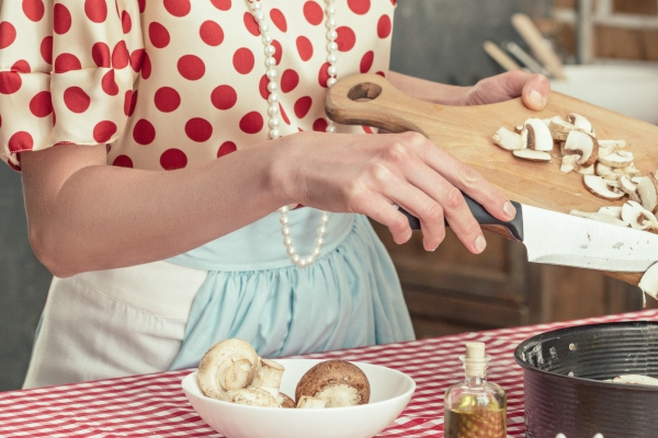 woman in apron chopping mushrooms