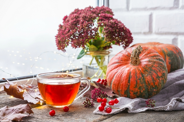 cup of tea on table with pumpkins and fall flowers