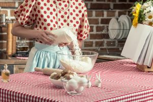 1950s housewife in red polka dress, aqua apron, standing at table cooking