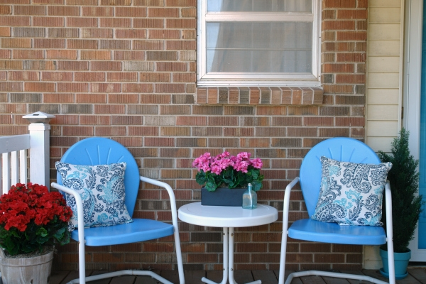two blue chairs with pillows and outdoor artificial plants on porch