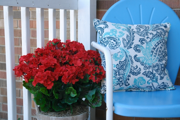 blue chair with pillow and red flowers