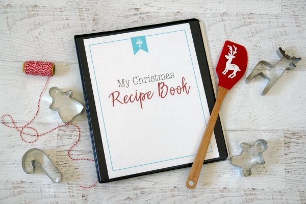 Christmas Recipe Book on white table with cookie cutters and spatula